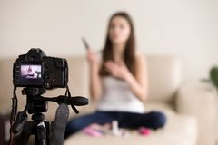 Young female videoblogger recording product review for blog. Young female videoblogger sitting on sofa, records commercial beauty product review for personal royalty free stock photo