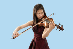 Young female violin player. Young asian woman playng the violin on blue background Stock Photo