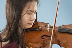 Young female violin player. Young asian woman playng the violin on blue background Stock Images