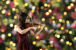 Young female violin player. Young asian female violin player, xmas lights in the background Royalty Free Stock Photography
