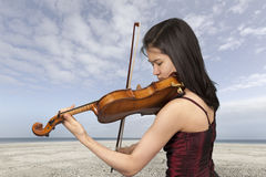 Young female violin player at the beach Royalty Free Stock Photos