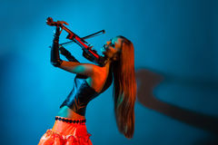 Young female violinist playing violin. On a blue background Royalty Free Stock Photography