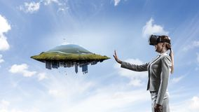 Young female in virtual reality. Young businesswoman wearing VR glasses with abstract landscape and cityscape object stock photo