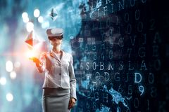 Young female in virtual reality. Young businesswoman wearing VR glasses beside a digital touch screen with graphs, diagrams, icons and ethereum symbols stock illustration