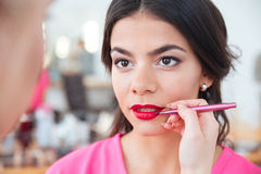 Young female visagiste applying red lipstick to lips of woman Stock Photography