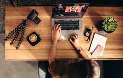 Young female vlogger editing her vlog on computer. Top view of female vlogger editing video on laptop. Young woman working on computer with coffee and cameras stock photo