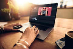 Young female vlogger editing her vlog on computer. Woman editing video on laptop computer for her vlog. Woman wearing fashionable rings working on laptop on a stock photography