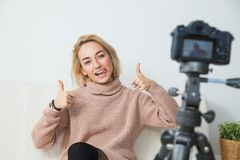 Young female vlogger next to camera at home. recording video for blog. Blogging concept. Young female vlogger next to video camera at home. Beautiful woman Royalty Free Stock Images