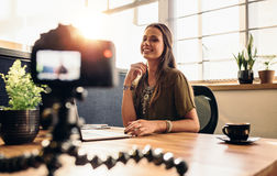 Young female vlogger recording content for her video blog. Young woman recording video for her vlog on a digital camera mounted on flexible tripod. Smiling Stock Photo