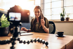 Young female vlogger recording content for her video blog. Young woman recording video for her vlog on a digital camera mounted on flexible tripod. Smiling Stock Photography