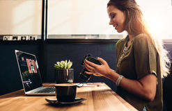 Young female vlogger watching her camera while editing her vlog. Side view of female vlogger looking at camera while editing video on laptop. Young woman working royalty free stock images