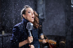 Young female vocalist sings into microphone Royalty Free Stock Photo