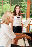 Young female voice student. An 11 year old girl taking voice lessons from a teacher Stock Photos