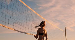 Young female volleyball players pass and spike the ball over the net on a sunny summer evening. Fit Caucasian girls. SLOW MOTION, LOW ANGLE, CLOSE UP, LENS FLARE stock footage