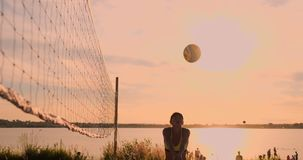 Young female volleyball players pass and spike the ball over the net on a sunny summer evening. Fit Caucasian girls. SLOW MOTION, LOW ANGLE, CLOSE UP, LENS FLARE stock video