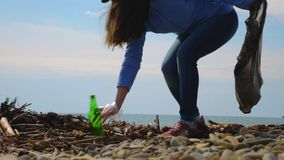 Young female volunteer collects garbage on the beach. Environmental protection and responsibility. Eco and day of Earth concept.