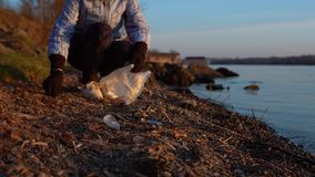 A woman volunteer collects garbage on the shore of the reservoir. A young female volunteer collects garbage on the shore of the reservoir in the evening at stock video footage