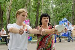 Young female volunteer shows middle-aged woman plus size how to properly hold fat monitor in their hands for proper measurement. Komsomolsk-on-Amur, Russia royalty free stock photography
