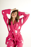 Young female waking up. Young woman waking up wearing a pink polka dotted bathrobe Stock Image