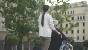 Young female on walk with disabled elderly male in wheelchair, family support