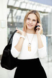 Young female walking in fashionable outfit making call on mobile Royalty Free Stock Photos