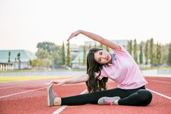 Young female  warming up on a running trac Royalty Free Stock Image