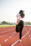 Young female  warming up on a running trac Stock Photo