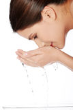 Young female washing her face with clear water Royalty Free Stock Photos