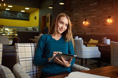 Young female is watching video on digital tablet during rest in modern coffee shop. Beautiful Caucasian woman working on net-book during morning breakfast in Stock Image
