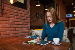 Young female is watching video on digital tablet during rest in modern coffee shop. Hipster girl with mobile phone and digital tablet, while is sitting at the Stock Photography