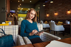 Young female is watching video on digital tablet during rest in modern coffee shop Royalty Free Stock Image