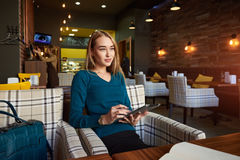 Young female is watching video on digital tablet during rest in modern coffee shop Stock Photos
