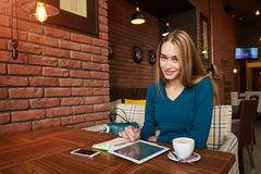 Young female is watching video on digital tablet during rest in modern coffee shop. Stylish hipster girl is using for remote freelance job portable net-book Stock Images