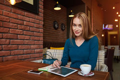 Young female is watching video on digital tablet during rest in modern coffee shop. Young woman journalist is looking thought window while is thinking about Royalty Free Stock Photo