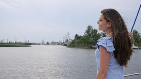 Young female waving hand hello for friends, girl with long hair on background of river, lady stands with back near water stock video footage