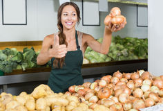 Young female wearing apron picking onion bulbs Stock Photos
