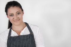 Young female wearing a blue strip, apron, smiling Royalty Free Stock Photo