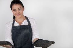 Young female wearing a blue strip, apron, smiling Royalty Free Stock Image