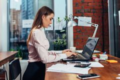 Young female wearing formal clothes working on laptop typing emails sitting at her workplace Stock Photos