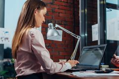 Young female wearing formal clothes working on laptop typing emails sitting at her workplace Royalty Free Stock Photos