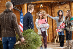 Young female welcomes guests. For Christmas holidays Royalty Free Stock Photos