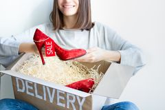 Young female woman adult customer buyer smiling received purchased new red high heels with sale label in delivery box ordered in stock photography