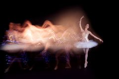 Ballerina dancer on stage with silhouette trail. Young female / woman / girl ballerina in a white pack / tutu solo dancing doing stand on toes and leaves light stock photography