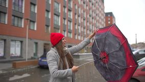 Young female woman, girl with umbrella standing outdoors. The gust of wind pulls umbrella out of hand. umbrella girl. Bad miserable weather, high wind and rain stock video footage