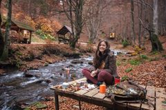 Young female woman making coffee in aluminium coffee maker outdoors. In autumn forest Royalty Free Stock Photography