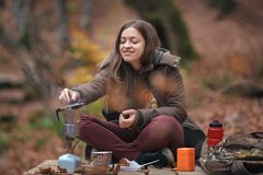 Young female woman making coffee in aluminium coffee maker outdoors. In autumn forest Stock Image