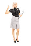 Young female worker holding clipboard and giving thumb up Stock Photo