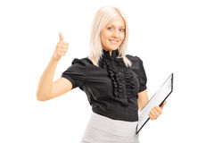 Young female worker holding clipboard and giving thumb up Stock Images