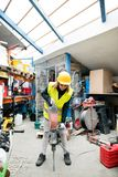 Female worker with jackhammer in a warehouse. Stock Photos