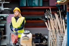 Female worker with jackhammer in a warehouse. Stock Photo